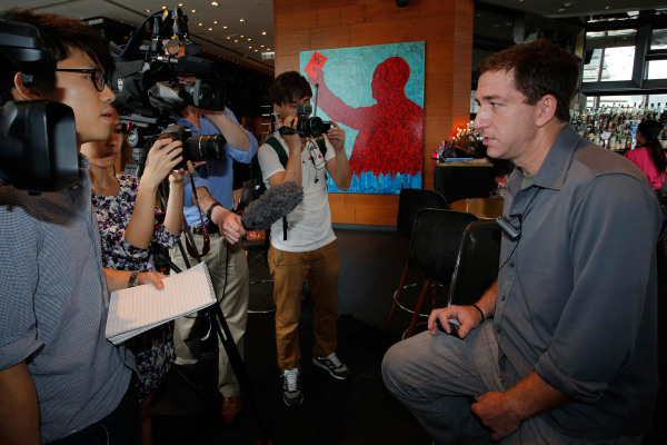 Image: Glenn Greenwald, right, a reporter for The Guardian newspaper, speaks to media at a hotel in Hong Kong June 10, 2013