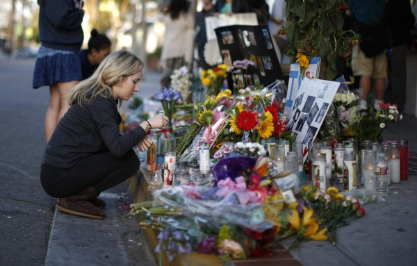 Image: A woman lights a candle at memorial for UCSB shooting victim