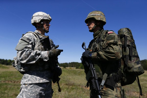 Image: Captain Tomasz Neuman, company commander of Polish 6 Airborne Brigade, and Captain Tadeusz Borawski, company commander of the U.S. Army's 173rd Infantry Brigade Combat Team, speak in Poland