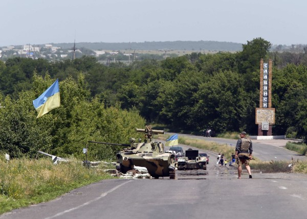 Image: Ukrainian servicemen patrol at a checkpoint outside the eastern Ukrainian town of Slaviansk
