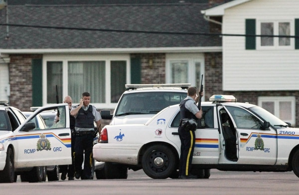 Image: Codiac RCMP officers take cover behind their vehicle in Moncton