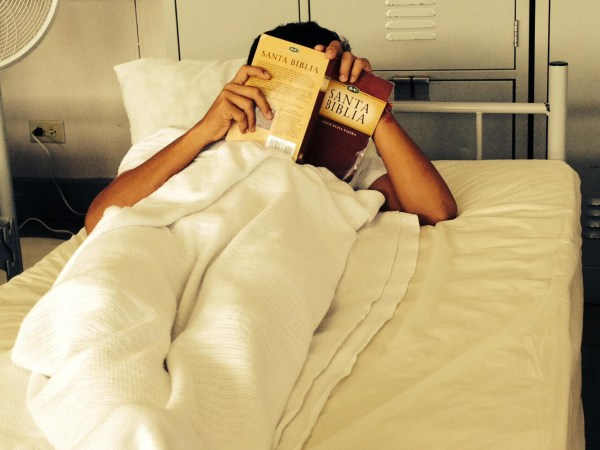Image: A young boy reading his bible at the Joint Base San Antonio Lackland Shelter