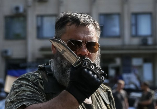 Image: A pro-Russian rebel holds a knife as he stands near a local government building in downtown Kramatorsk