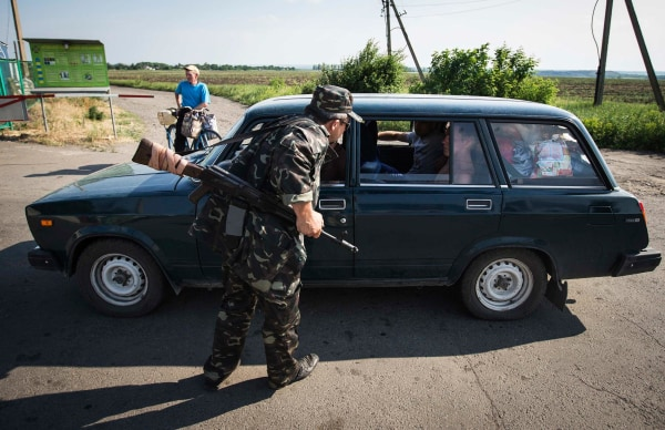 Image: An armed pro-Russian separatist speaks with passengers in a car leaving Ukraine at a border post abandoned by Ukrainian border guards at Chervonopartyzansk along the Ukraine-Russia border