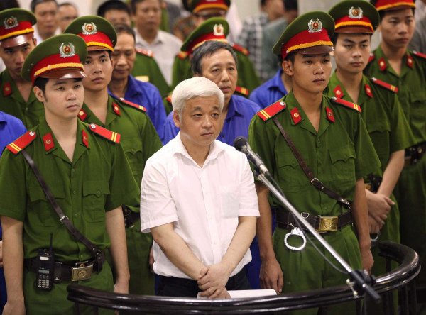 Image: Former Vietnamese banking tycoon Nguyen Duc Kien, 50, stands listening to the verdict read at the Hanoi People's Court