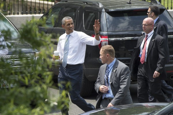 Image: President Barack Obama waves to members of the news media after making a surprise visit to a nearby Starbucks