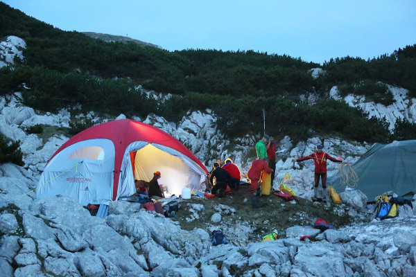 Image: Rescue workers gather at a tent near the entrance to the Riesending underground cave