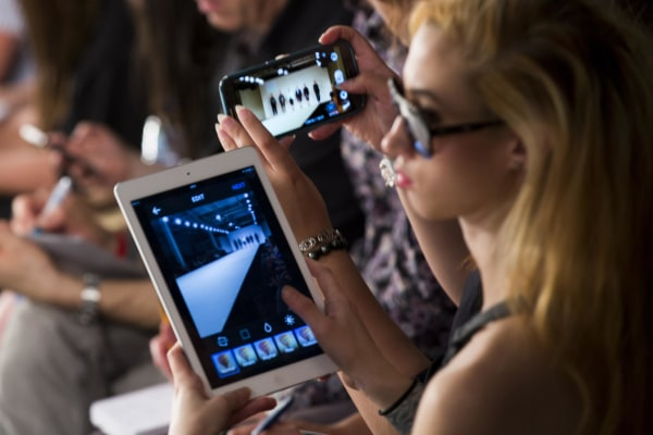 Image: A girl photographs the Kingston University show on an iPad during day 3 of Graduate Fashion Week 2014 at The Old Truman Brewery on June 2 in London, England.