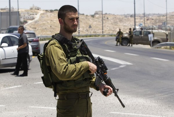 Image: An Israeli soldier stands guard at a junction near the West Bank city of Hebron