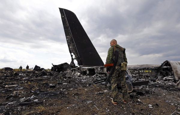 Image: Pro-Russian separatists walk at the site of the crash of the Il-76 Ukrainian army transport plane in Luhansk