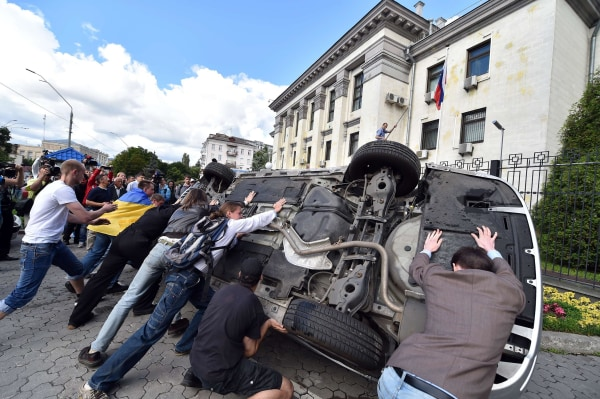 Image: People flip a car over during a rally against the Russian president in front of the Russian embassy in Kiev