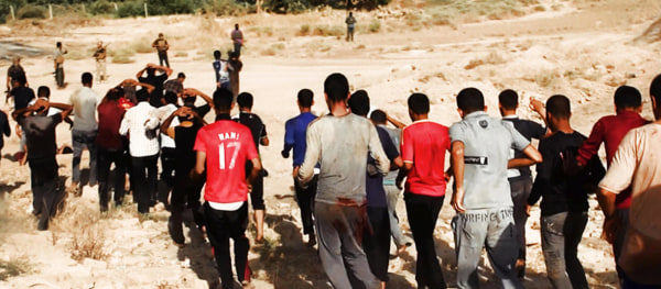 Image: Militants from ISIL lead captured Iraqi soldiers wearing plain clothes to an open field moments before shooting them in Tikrit.