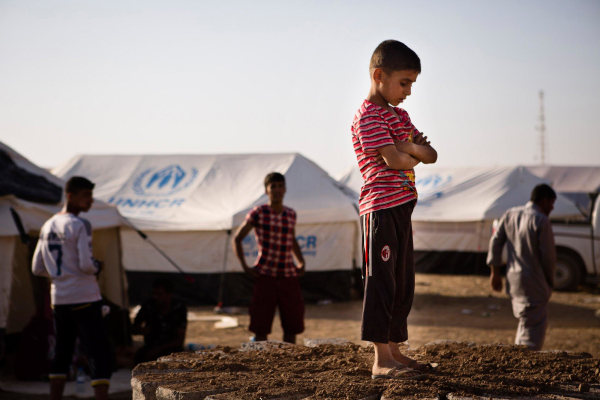 Image: A boy, who fled from the violence in Mosul, stands near tents in a camp for internally displaced people on the outskirts of Arbil in Iraq's Kurdistan region
