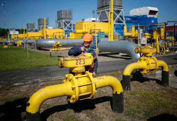 Image: File photo of a worker turning a valve at an underground gas storage facility near Striy