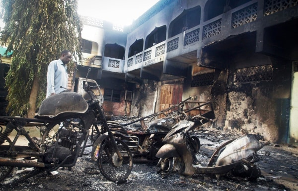 Image: The remains of destroyed vehicles and buildings in the town of Mpeketoni