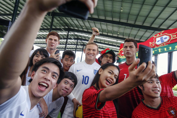 Image: Thai fans take selfies with wax figures of Steven Gerrard, Wayne Rooney and Cristiano Ronaldo in Bangkok