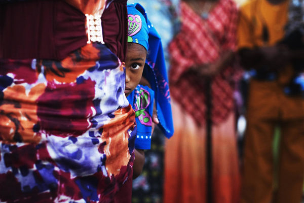Image: A girl from the African Hebrew Israelite community hides behind an adult during a celebration for the holiday of Shavuot in Dimona