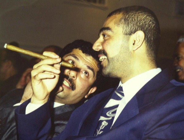 Saddam Hussein's eldest son Odai speaks with his younger brother Qusai