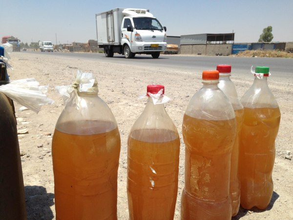 Image: Bottles of black-market fuel for sale on the side of a highway near Mosul, Iraq.