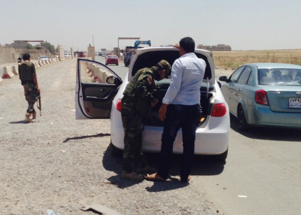 Image: Kurdish security forces check cars along a highway outside Mosul, Iraq.