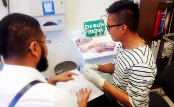 John Guigayoma (far right) gives an HIV test to a client at Asian & Pacific Islander Wellness Center in San Francisco.