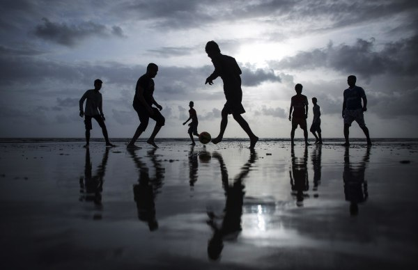 Image: People are silhouetted as they play football at a beach along the Arabian Sea in Mumbai