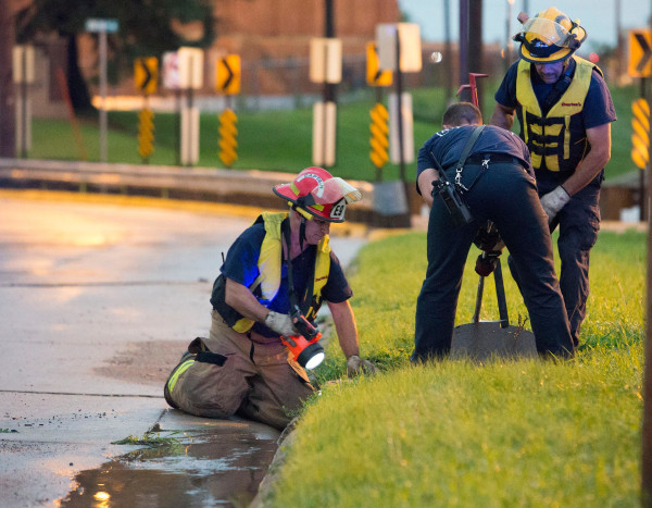 Image: Cedar Rapids Firefighters open a manhole cover as they try to locate a child reportedly swept into a sewer by storm water near the intersection of E Avenue and Oakland Road NE in Cedar Rapids