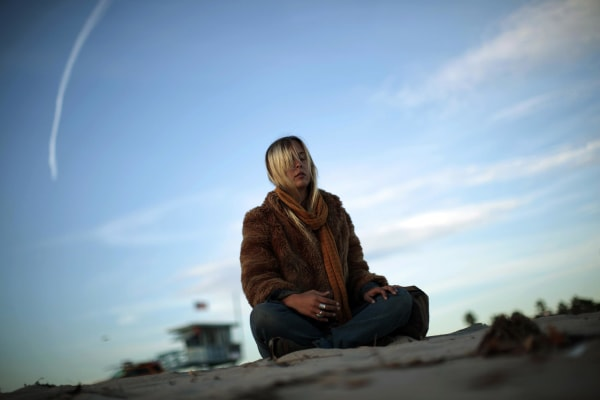 A woman meditates at sunset on Venice Beach in Los Angeles, on New Year's Eve