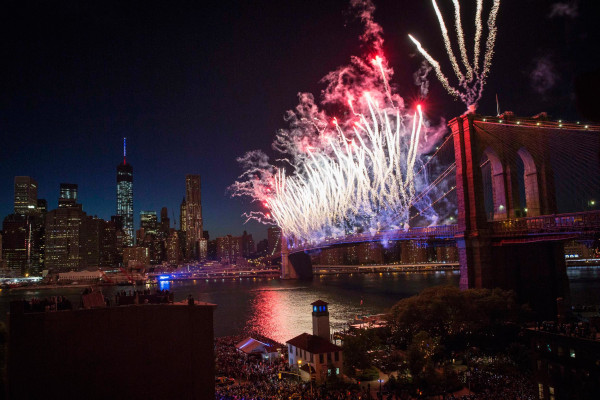 """Image: Fireworks explode over Brooklyn Bridge and East River during """"Macy's Fourth of July Fireworks Spectacular"""" in Brooklyn borough of New York"""