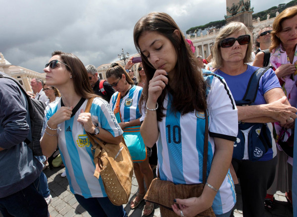 Image: Faithful wearing Argentina soccer team jerseys pray as Pope Francis delivers the Angelus praye