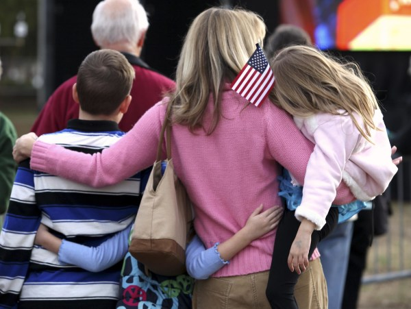 Image: A woman huddles with her children while watching a speech next to the Myrtle Beach Convention Center in Myrtle Beach on Jan. 16, 2012.
