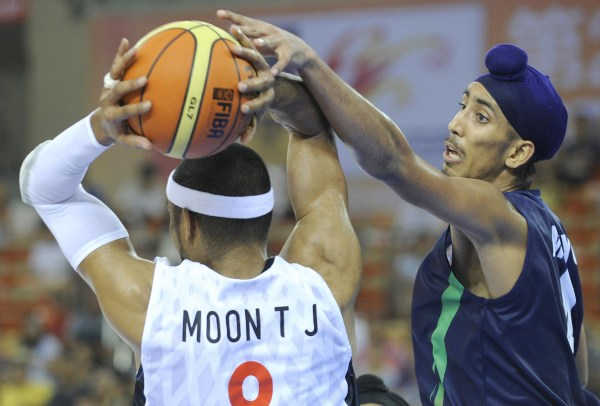 Image: Moon Tae Jong of South Korea passes a ball as Amjyot Singh of India defends during their preliminary round match between South Korea and India at the 26th Asian Basketball Championships in Wuhan in China's central Hubei province on Sept. 17, 2011.