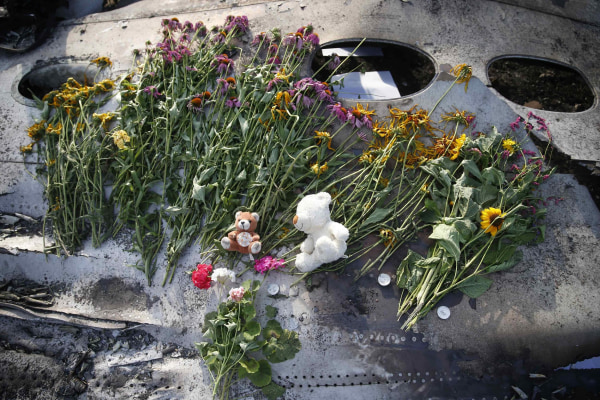 Image: Flowers and mementos left by local residents lie on wreckage at the crash site of Malaysia Airlines Flight MH17, near the settlement of Grabovo in the Donetsk region