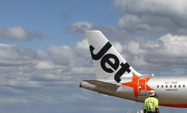 Image: An airport worker stands in front of a Jetstar passenger plane at Avalon Airport in Melbourne on March 19, 2010 .