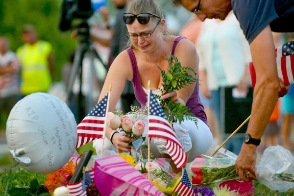 Image: Gail Krull of West St. Paul, Minn. a niece of Mendota Heights, Minn. Police Officer Scott Patrick, cries as she lays a bouquet of roses on a makeshift memorial