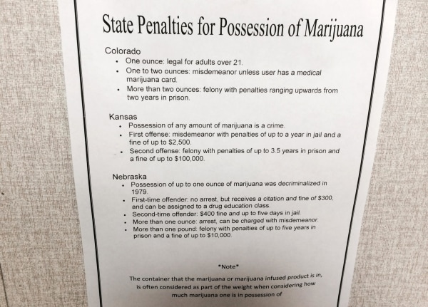 Image: A sign warning about nearby state's pot laws hangs in the dispensary