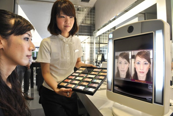 Image: An employee of Japan's cosmetics giant Shiseido demonstrates the company's virtual make-up system