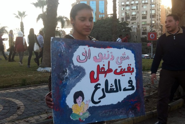 """Image: A homeless girl holds a sign reading: """"It is not my fault that I became a street child"""""""