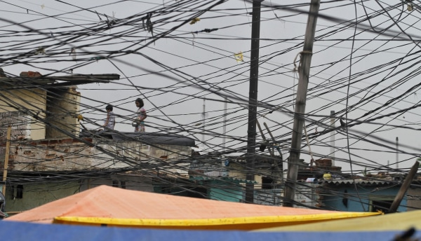 Image: Tangled overhead electric power cables are pictured at a residential area as children stand on the roof of a house in Noida