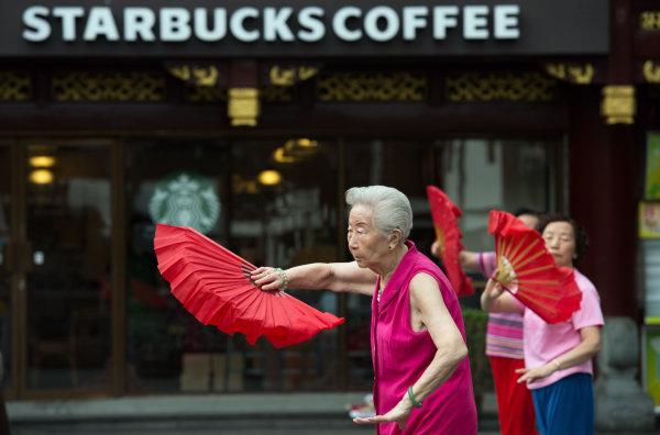Image: Women do morning exercises in front of a Starbucks restaurant