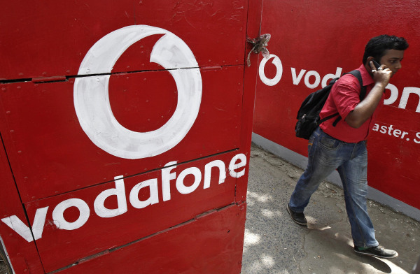 Man speaks on his mobile phone as he walks past the logos of Vodafone painted on a roadside wall in Kolkata