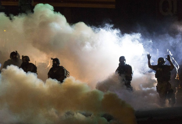 Image: Riot police clear a street with smoke bombs while clashing with demonstrators in Ferguson, Missouri