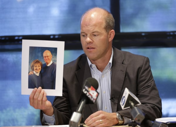 Image: Attorney Paxton Guymon holds a photograph of Jim and Jan Harding