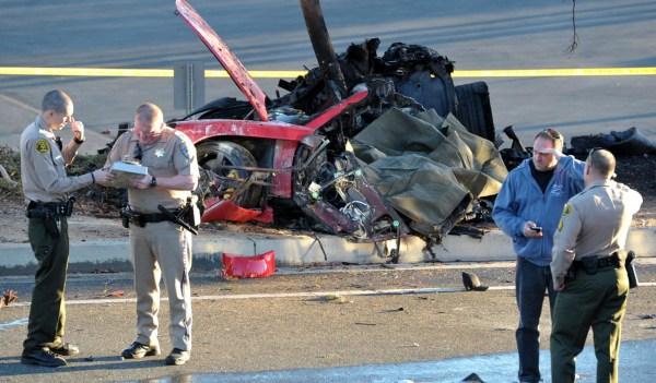Image: Sheriff deputies work near the wreckage of a Porsche