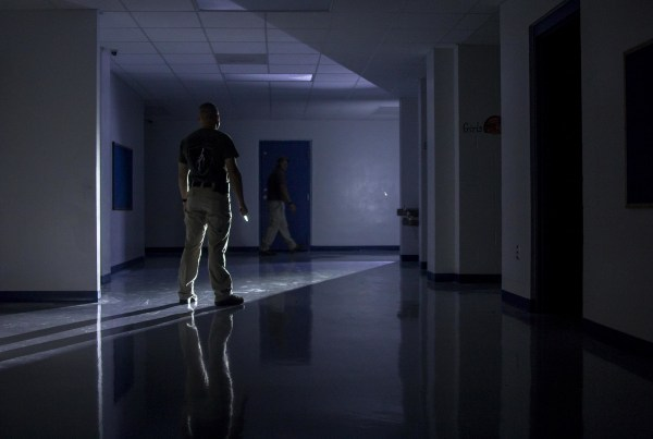 IMAGE: Shield Solutions instructor Jason Long stands at the end of a darkened hallway holding a knife, representing a school invader, while school employees practice their tactical maneuver