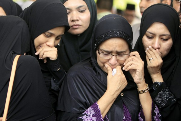 Image: Family members of Nur Shazana, a Malaysia Airlines crew member who was among the victims onboard Flight MH17, cry during a burial ceremony
