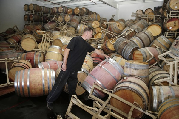 Image: Cellar worker Daniel Nelson looks over toppled barrels