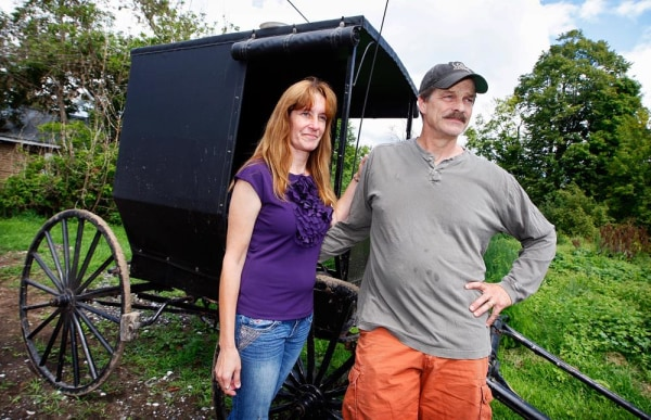 Image: Jeffrey M. and Pamela L. Stinson pose for a portrait outside an Amish buggy