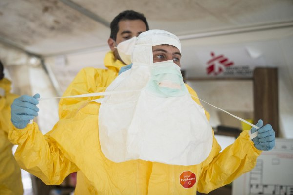 Image: A Doctors Without Borders logistician puts on protective clothing at an Ebola treatment center in Guinea