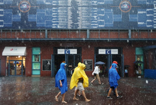 Image: Tennis fans walk barefoot as play is suspended during the 2014 U.S. Open tennis tournament.